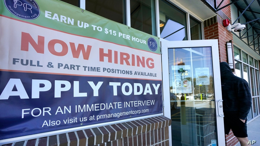 """FILE - A man walks into a restaurant displaying a """"Now Hiring"""" sign, in Salem, New Hampshire, March 4, 2021."""