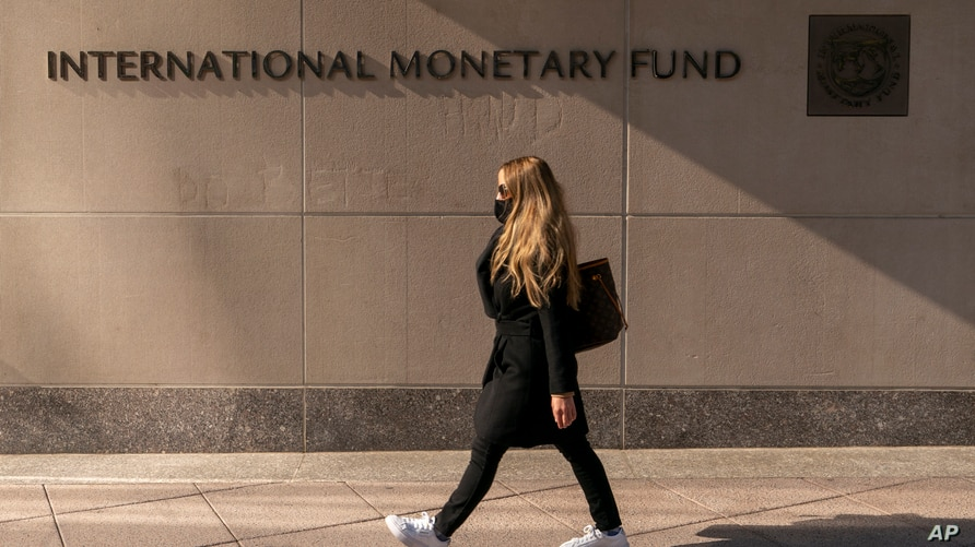 FILE - Signage is seen on the International Monetary Fund building, in Washington, April 5, 2021.