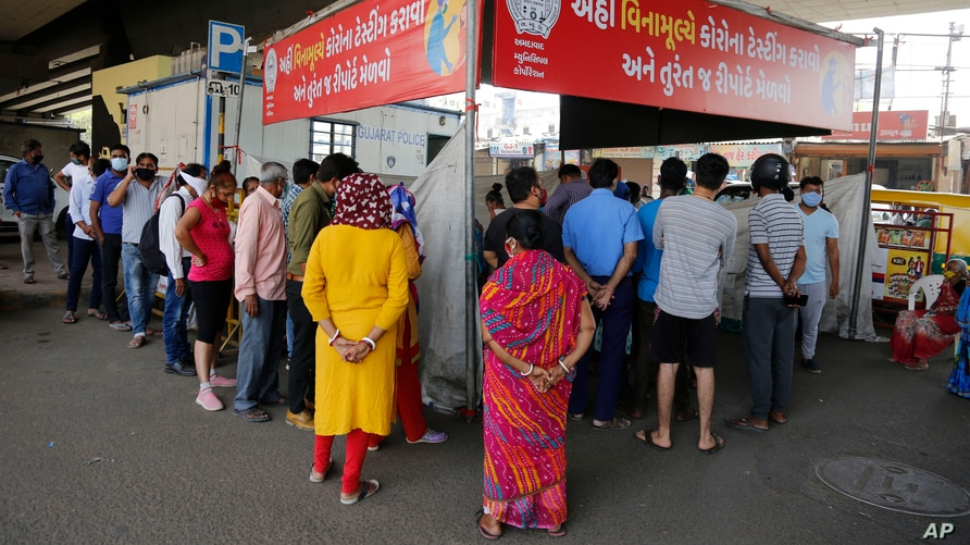 People stand in a queue to get tested for the coronavirus, in Ahmedabad, India, April 9, 2021.
