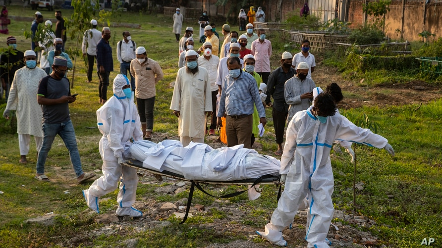 Municipal workers prepare to bury the body of a person who died of COVID-19, in Gauhati, India, April 25, 2021.