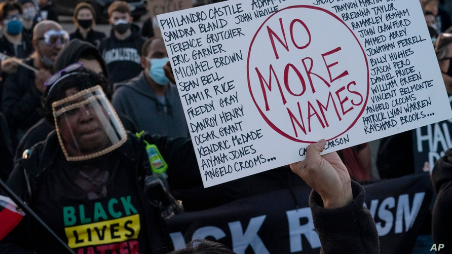A demonstrator holds up a sign bearing the names of people who died during police incidents, during a protest over the fatal shooting of Daunte Wright during a traffic stop, in Brooklyn Center, Minnesota, April 16, 2021.