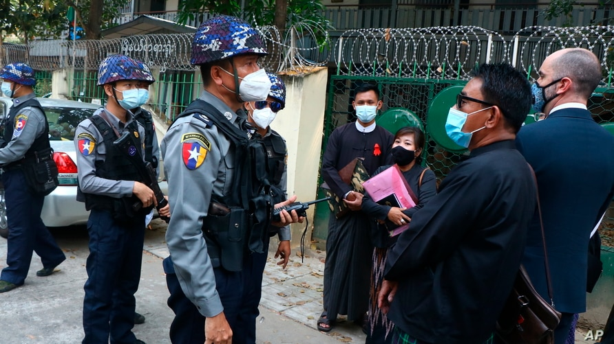 Myanmar police talk to people gathering outside the Kamayut court in Yangon, March 12, 2021.
