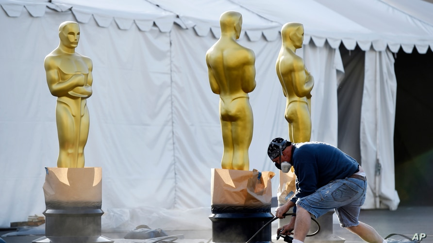 FILE - A scenic artists prepares Oscar statues off of Hollywood Boulevard for last years's 92nd Academy Awards, at the Dolby Theatre, Feb. 5, 2020, in Los Angeles, California.
