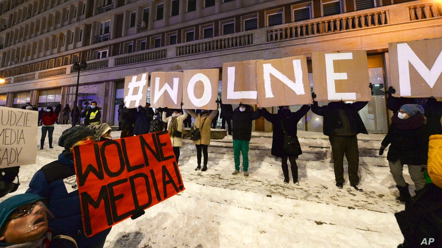 "FILE - Protesters with signs reading ""Free Media"" gather outside Poland's state TVP building in Warsaw, Poland, Feb. 10, 2021."