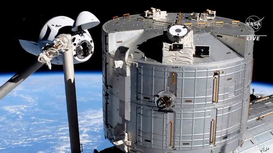 In this image from NASA TV, the SpaceX Crew Dragon capsule, left, approaches the International Space Station, April 24, 2021.