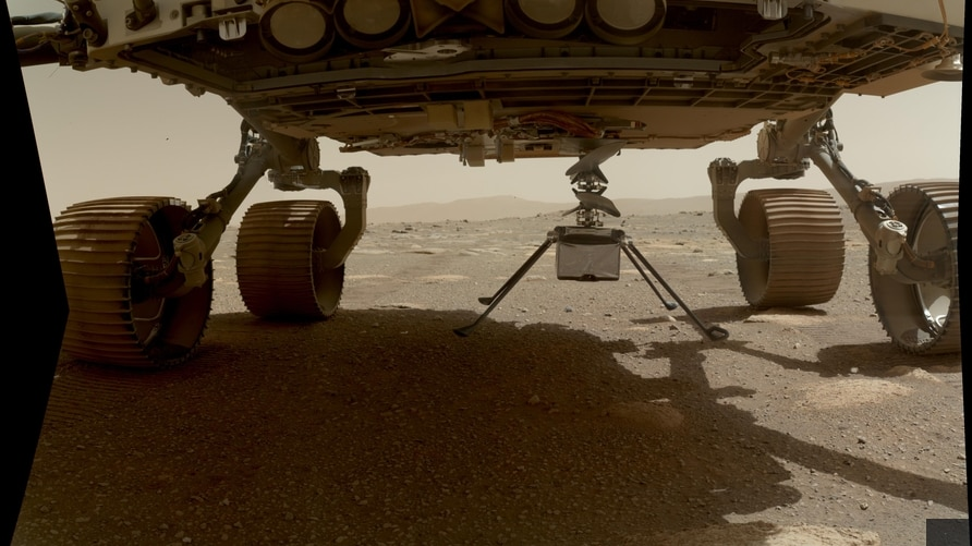 NASA's Ingenuity helicopter can be seen here with all four of its legs deployed before dropping from the belly of the Perseverance rover on March 30, 2021.