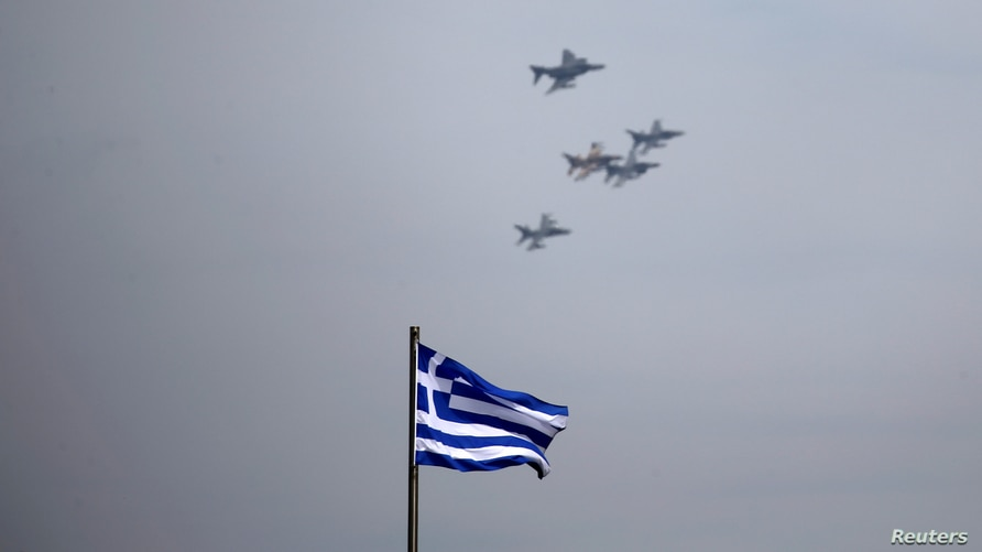 FILE - A Greek national flag flutters as a formation of fighter jets fly over Athens, Greece, April 4, 2017. Israel and Greece on Sunday signed their biggest ever defense procurement deal.