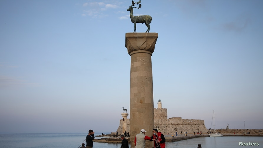 People wearing protective face masks bump elbows next to the statue of a deer at the entrance to Mandraki harbor, amid the COVID-19 pandemic, on the island of Rhodes, Greece, April 13, 2021.