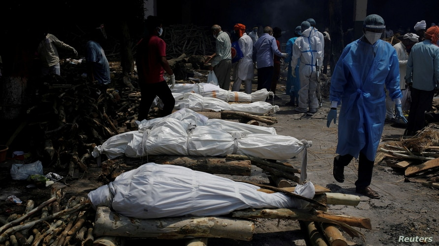 A health worker wearing personal protective equipment (PPE) walks past the funeral pyres of those who died from the COVID-19 during a mass cremation at a crematorium in New Delhi, India, April 26, 2021.