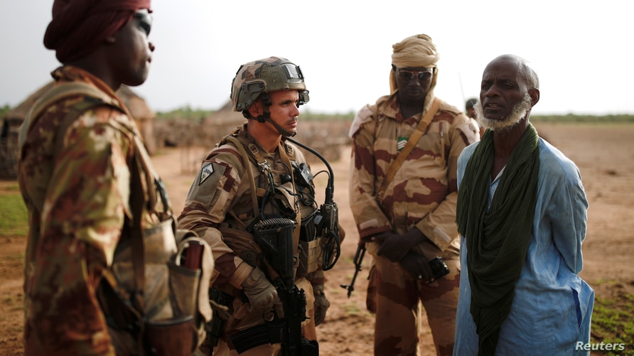 """FILE - Malian Armed Forces (FAMa) and French soldiers of the """"Belleface"""" Desert Tactical Group (GTD) conduct an area control operation in the Gourma region during the Operation Barkhane in Ndaki, Mali, July 29, 2019."""