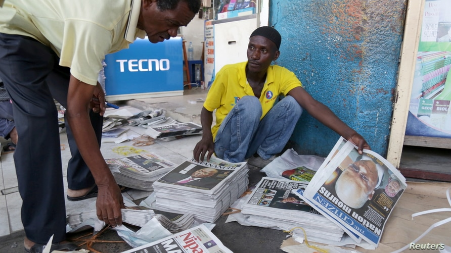 Vendors arrange copies of newspapers following the death of Tanzania's President John Magufuli in Dar es Salaam, March 18, 2021.