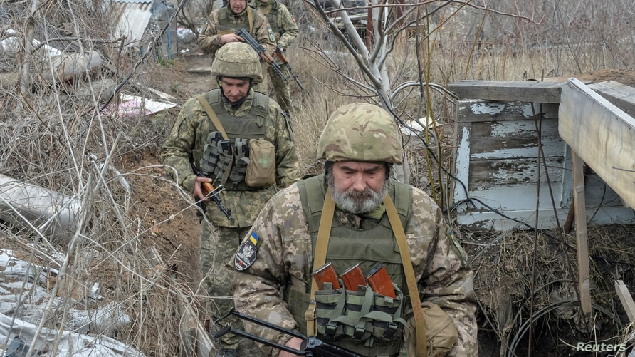 Service members of the Ukrainian armed forces walk on the line of separation from pro-Russian rebels near Donetsk, Ukraine, April 11, 2021.