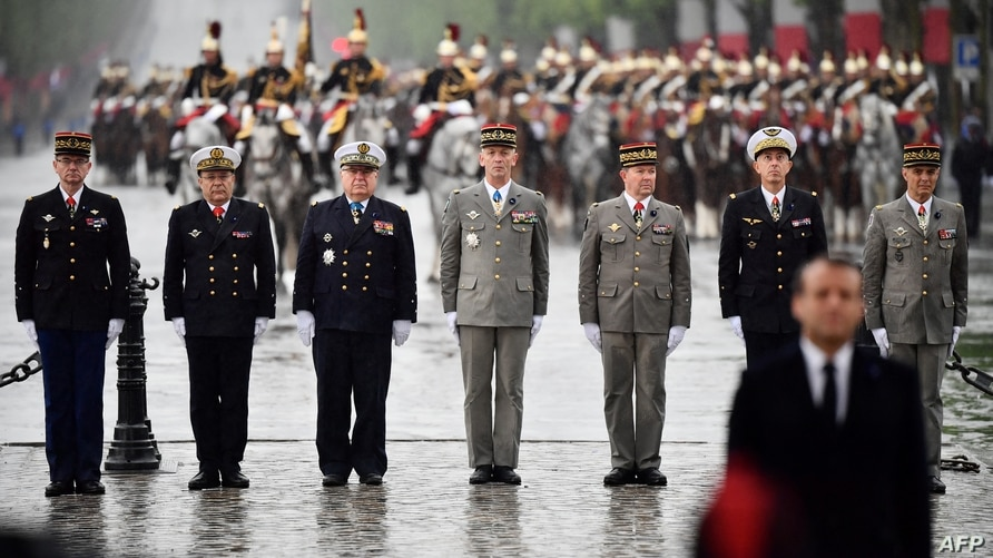 French generals and admirals stand guard behind French President (front right) at the tomb of the unknown soldier under the Arc…