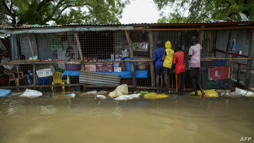 Children buy food at a shop in a flooded area after the Nile river overflowed after continuous heavy rain which caused…