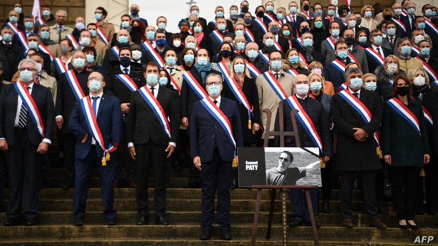 National Assembly president Richard Ferrand (C) stands among French MPs near a photo of late teacher Samuel Paty, as they pay…