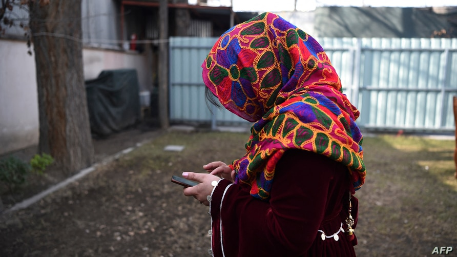 In this photo taken on January 19, 2021, an Afghan journalist, who fled from her home in central Afghanistan, uses a mobile…