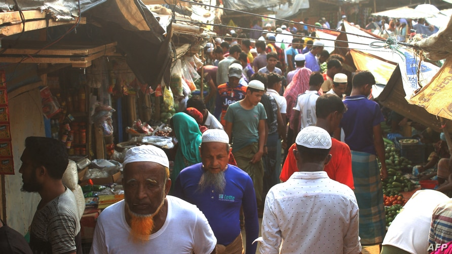 Rohingya refugees walk in market area inside a refugee camp in Ukhia on April 6, 2021 during the second day of weeklong …