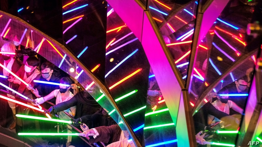 """Star Wars fans display their light sabres to mark a """"May the 4th be with you"""" event, at the Taipei 101 commercial building, the…"""