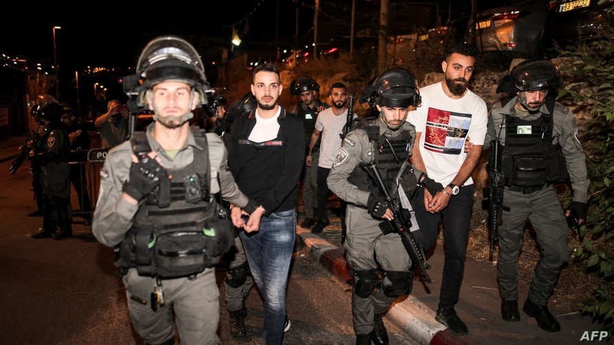 This picture taken on May 6, 2021 shows Israeli security forces detaining Palestinian protesters who were demonstrating in…