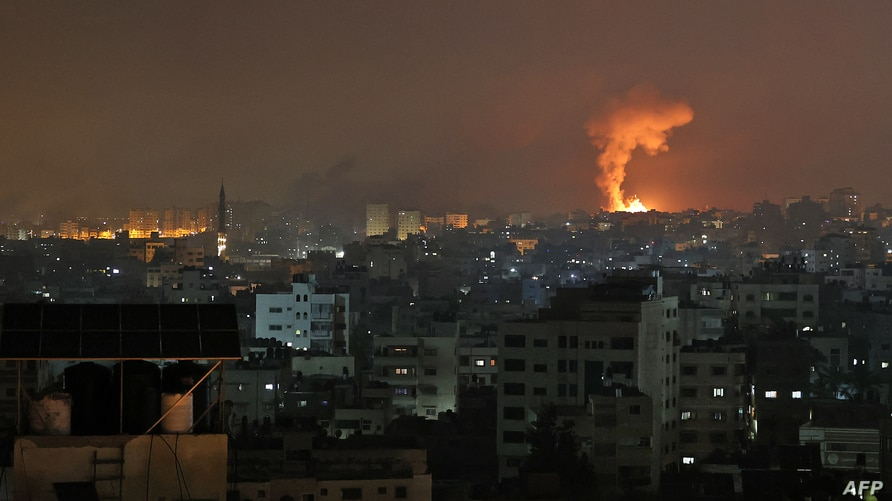 An explosion lights the sky following an Israeli air strike on Beit Lahia in the northern Gaza Strip on May 14, 2021. (Photo by…