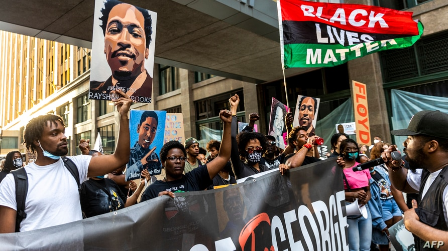 People raise their fists and hold signs and a banner as they march during an event in remembrance of George Floyd in…