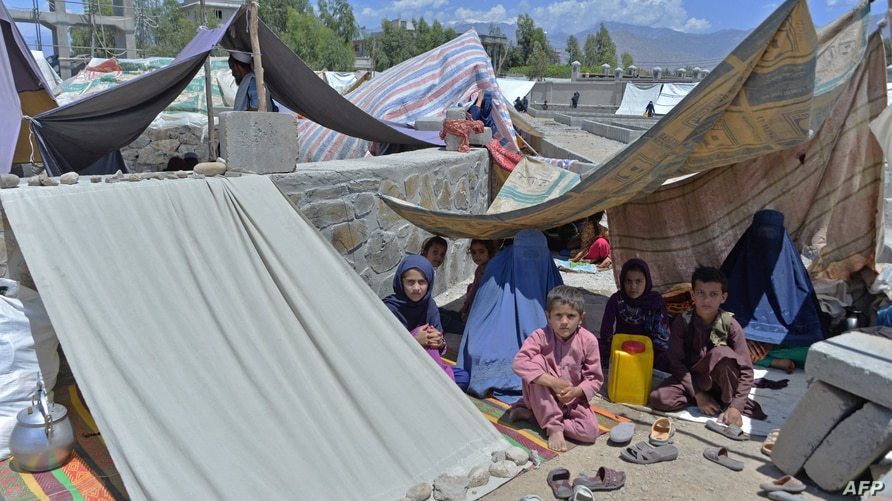Afghan families who have been displaced due to fighting between Taliban and Afghan forces, take temporary shelter at a market…