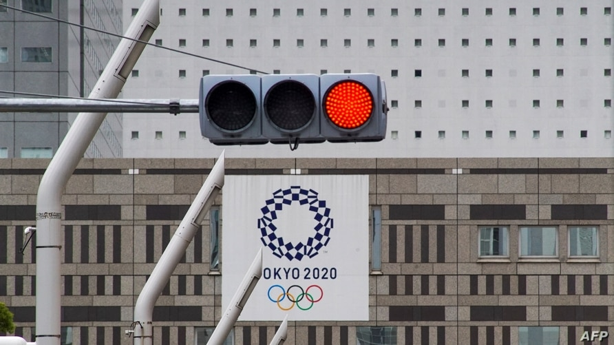 A red traffic light lights up on a street near the Tokyo Metropolitan Government Building displaying a banners of Tokyo 2020…