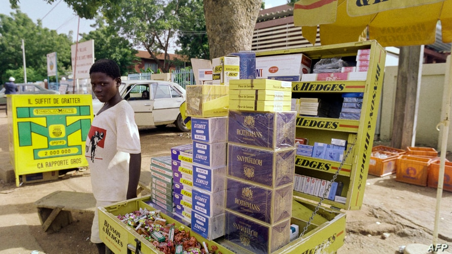 FILE - A young boy sells cigarettes in the streets of Ouagadougou.