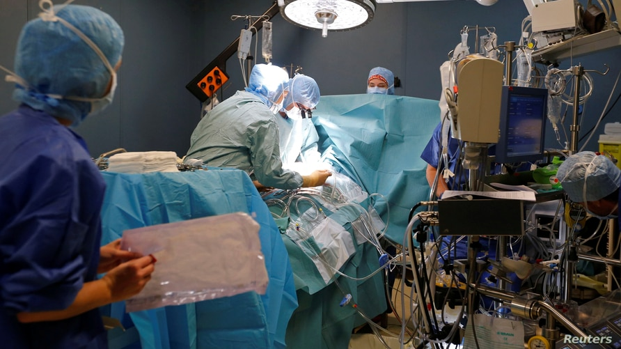 FILE - Medical team perform a heart surgery in an operating room at the Saint-Augustin clinic in Bordeaux, France.