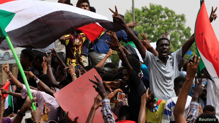 People shout slogans as tens of thousands of people march on the streets demanding the ruling military hand over to civilians,…