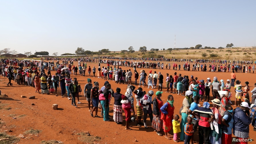People stand in a queue to receive food aid, during the coronavirus disease (COVID-19) outbreak at the Itireleng informal…