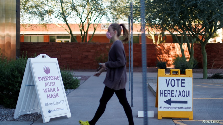 A woman walks to cast her ballot at the register of voters during early voting in Phoenix, Arizona, October 29, 2020.