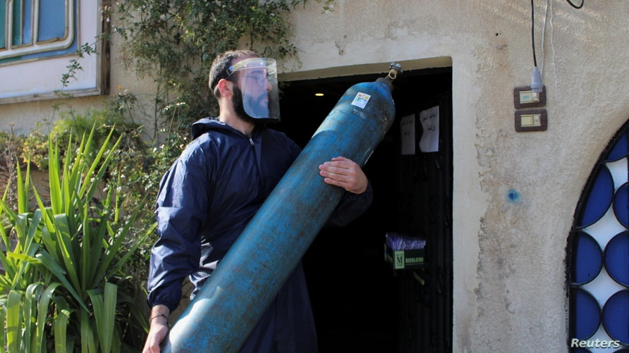 A volunteer carries an oxygen cylinder, to be delivered to a patient suffering from the coronavirus disease (COVID-19) and…