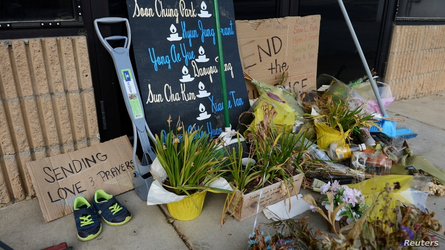 Dried flowers, signs and several brooms, squeegees and shovels block the entry of the Aromatherapy Spa in Atlanta, four weeks…