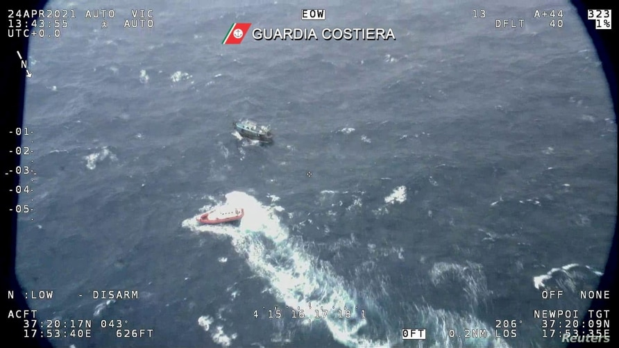 A fishing boat carrying around 100 migrants is seen from Italian coast guard helicopter during a search and rescue operation in…
