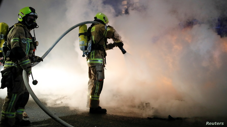 Firefighters work to extinguish a fire during a left-wing May Day demonstration, as the spread of the coronavirus disease …