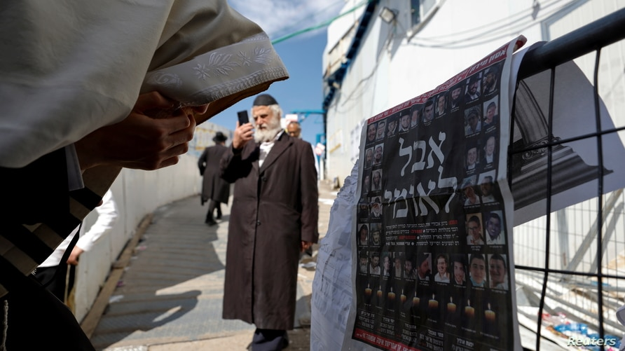 """Ultra-Orthodox Jewish man reacts in front of a newspaper's front page with the Hebrew words """"National Mourning"""", at the site…"""
