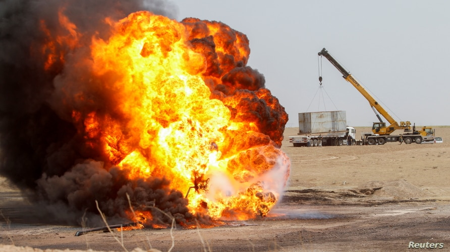 Flames and smoke rise from oil wells inside the Bai Hassan oilfield, which was attacked by militants, close to the northern…