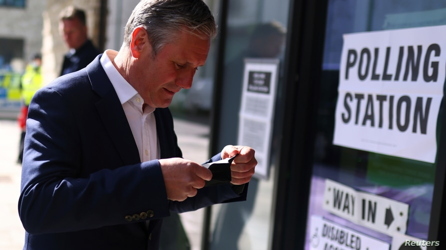 Britain's Labour Party leader Keir Starmer puts on a protective mask as he arrives at a polling station to vote during local…