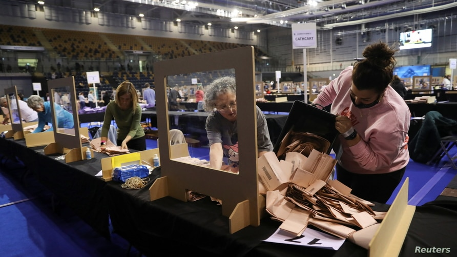 Election staff members count votes for the Scottish Parliamentary election at a counting centre in Glasgow, Scotland, Britain,…