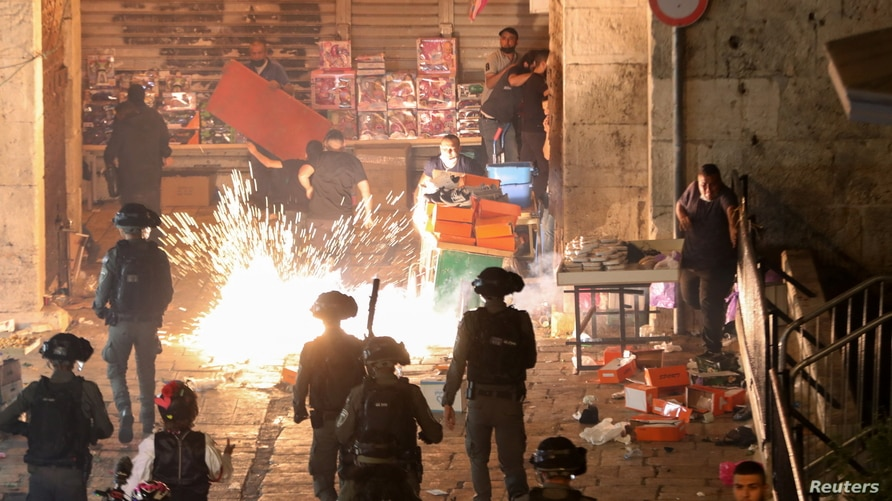 Palestinians react as Israeli police fire a stun grenade during clashes at Damascus Gate on Laylat al-Qadr during the holy…