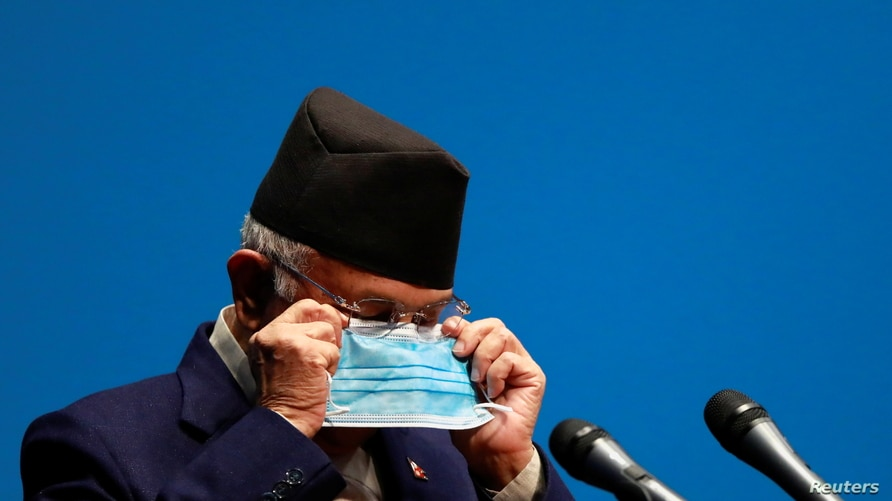 Nepal's Prime Minister Khadga Prasad Sharma Oli, also known as K.P. Oli, puts on a new face mask during his speech before a confidence vote at the parliament in Kathmandu, Nepal May 10, 2021.