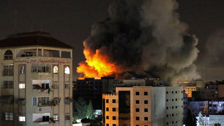 Smoke rises from a tower after it was hit by Israeli air strikes amid a flare-up of Israeli-Palestinian violence, in Gaza City…