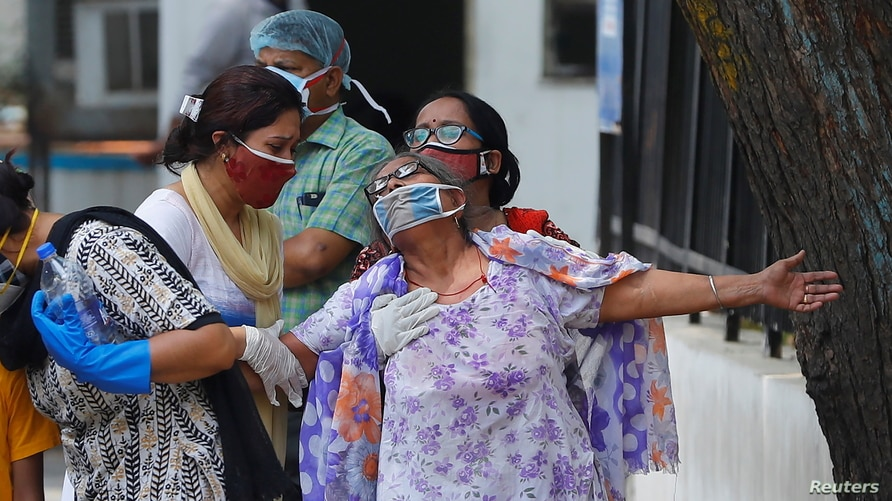 A woman mourns after seeing the body of her son who died due to the coronavirus disease (COVID-19), outside a mortuary of a…