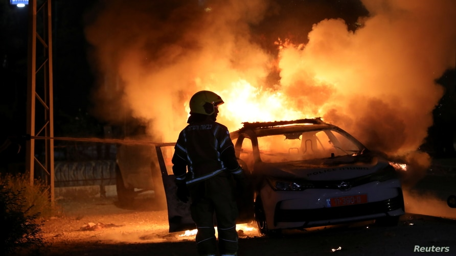 An Israeli firefighter stands near a burning Israeli police car during clashes between Israeli police and members of the…