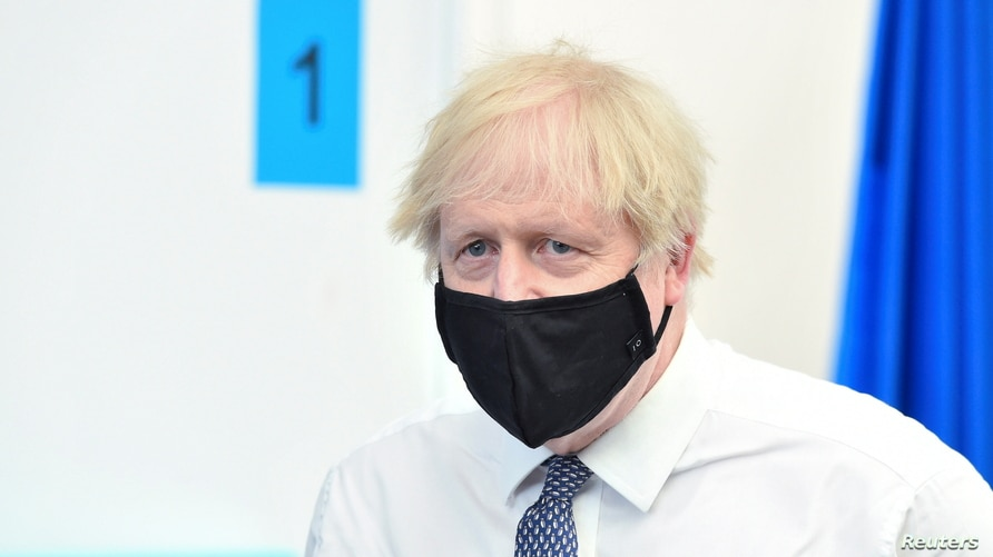 Britain's Prime Minister Boris Johnson looks on as he visits a coronavirus disease (COVID-19) vaccination site at the Business…