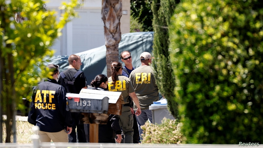 ATF and FBI agents approach the scene of the Santa Clara Valley Transportation Authority mass shooting suspect's house, after a fire at the home of the suspect erupted at about the same time as the shooting, in San Jose, California, May 26, 2021.