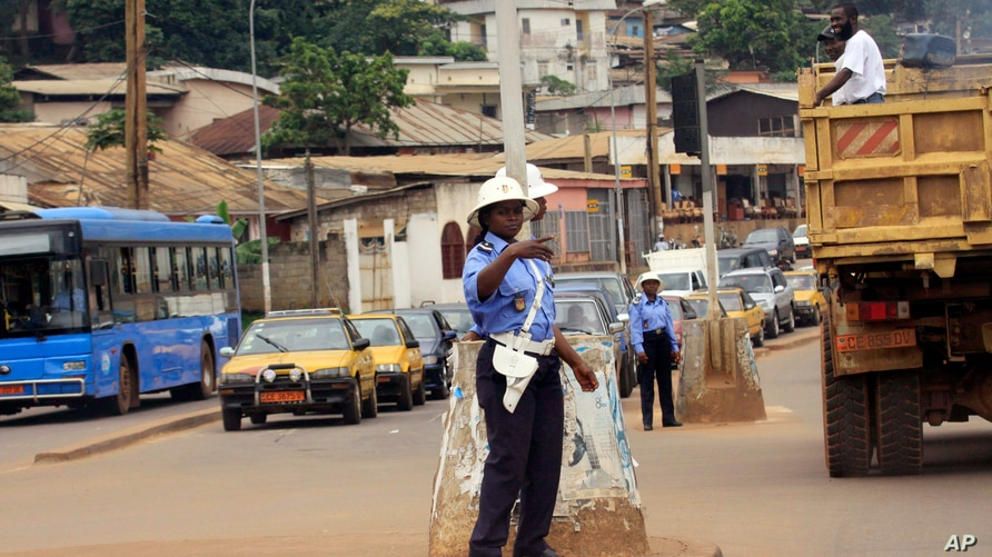 FILE - A police officer directs traffic in Yaounde, Cameroon.