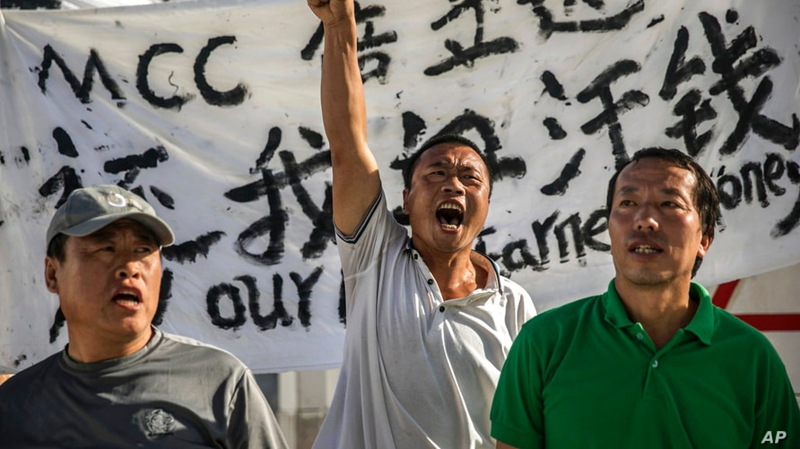 In this July 26, 2017, photo, Chinese laborers Jingbao Zhao, left, Xiaoli Wang, center, and Yongbo Sun, protest in front of the…