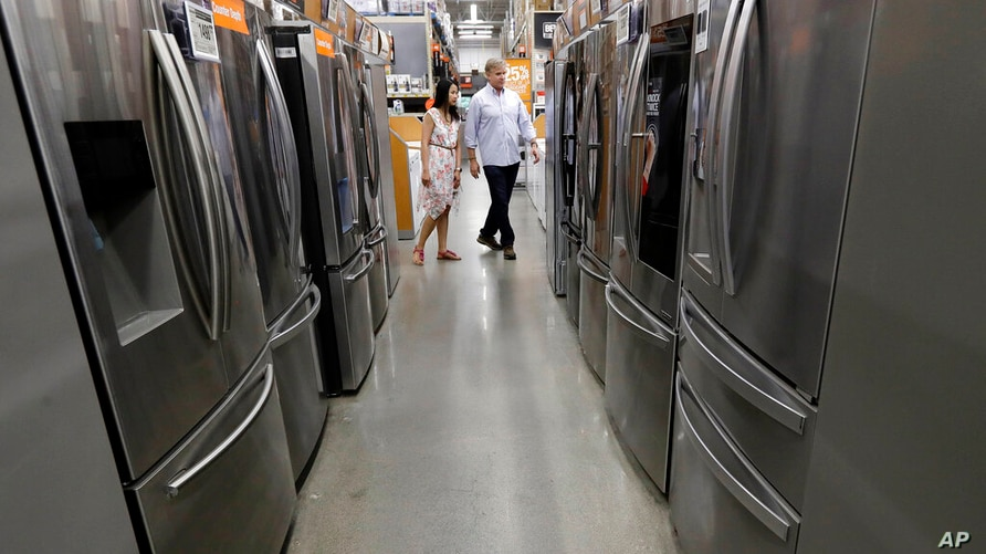 In this Monday, Sept. 23, 2019 photo shoppers examine refrigerators at a Home Depot store location, in Boston. On Friday, Sept…